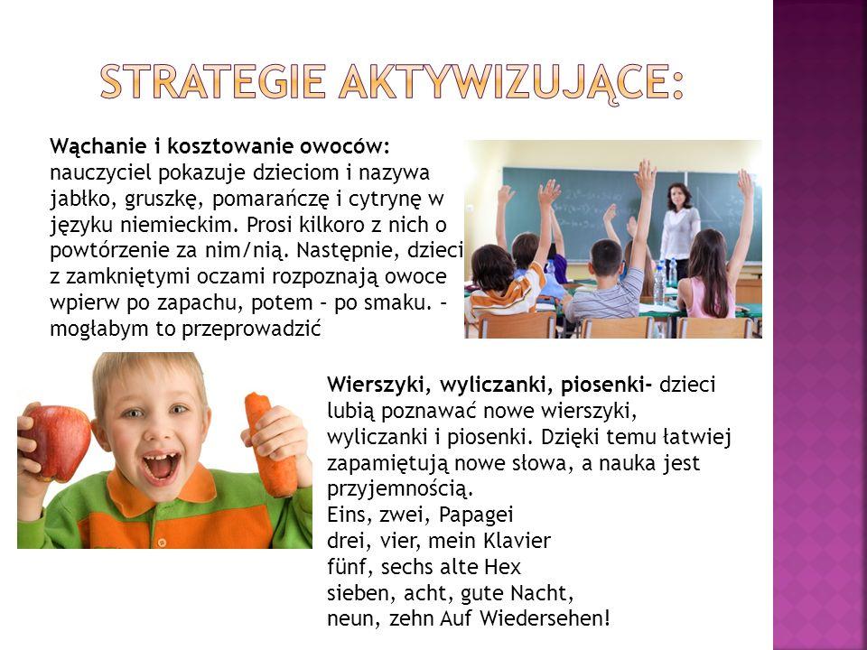 Wąchanie i kosztowanie owoców: nauczyciel pokazuje dzieciom i nazywa jabłko, gruszkę, pomarańczę i cytrynę w języku niemieckim. Prosi kilkoro z nich o