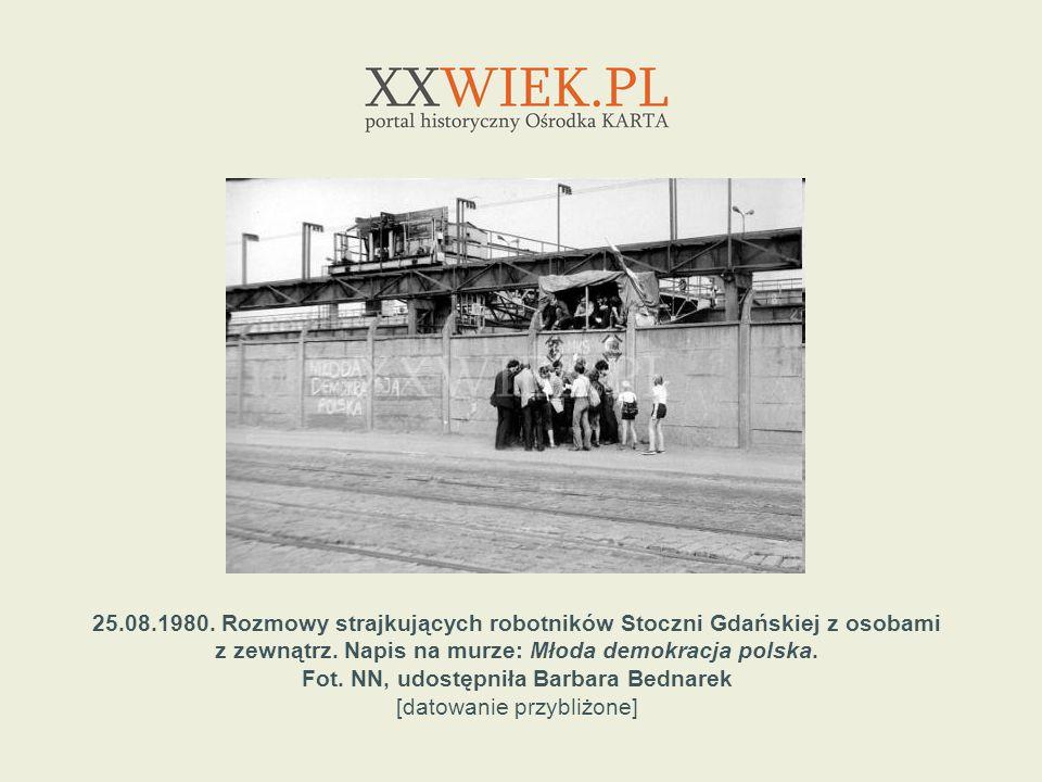 25.08.1980. Rozmowy strajkujących robotników Stoczni Gdańskiej z osobami z zewnątrz. Napis na murze: Młoda demokracja polska. Fot. NN, udostępniła Bar