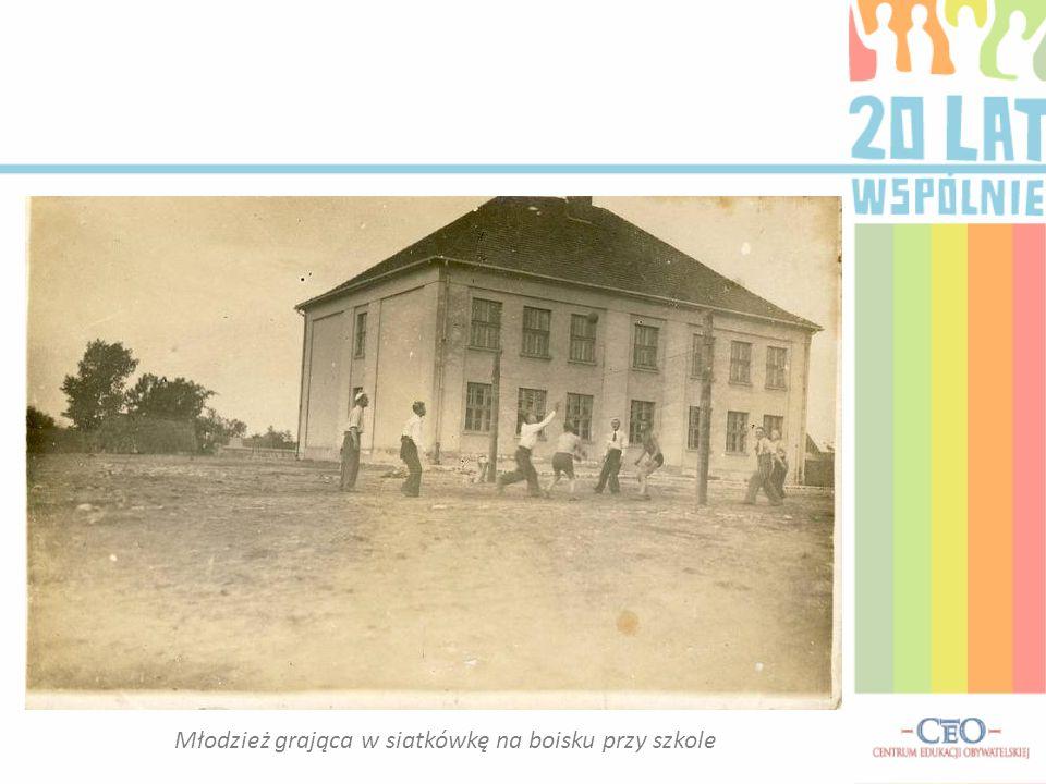 Młodzież grająca w siatkówkę na boisku przy szkole