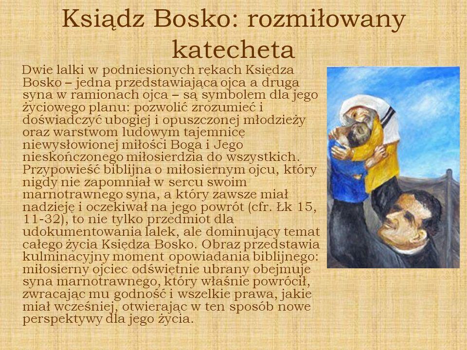 Ksiądz Bosko: rozmiłowany katecheta Dwie lalki w podniesionych rękach Księdza Bosko – jedna przedstawiająca ojca a druga syna w ramionach ojca – są sy