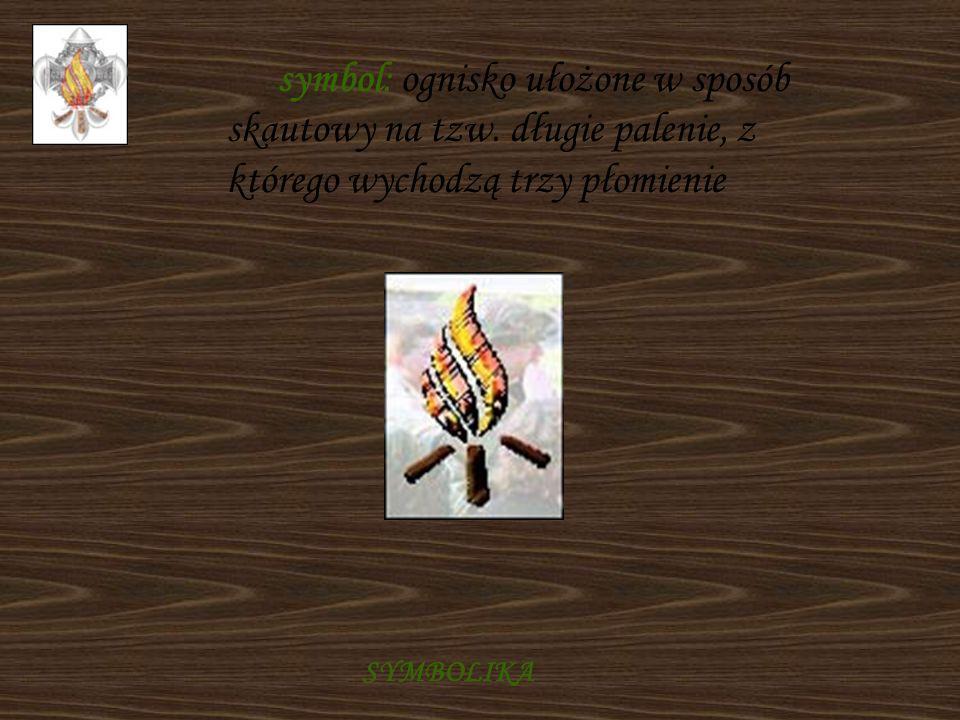 symbol: ognisko ułożone w sposób skautowy na tzw. długie palenie, z którego wychodzą trzy płomienie