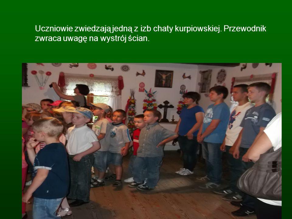 Uczniowie zwiedzają jedną z izb chaty kurpiowskiej. Przewodnik zwraca uwagę na wystrój ścian.