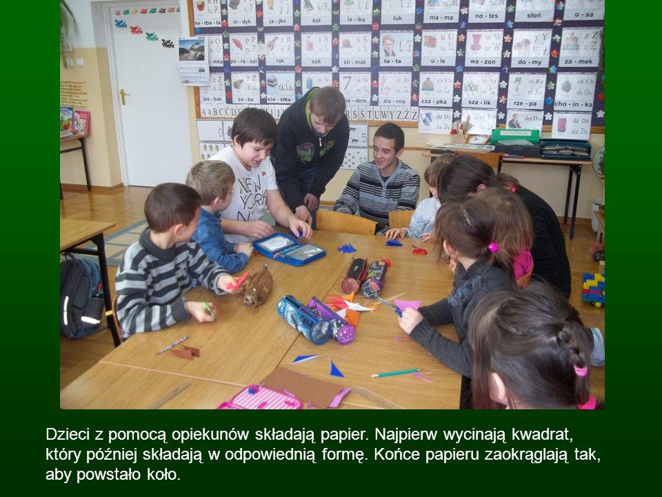 Dzieci z pomocą opiekunów składają papier. Najpierw wycinają kwadrat, który później składają w odpowiednią formę. Końce papieru zaokrąglają tak, aby p