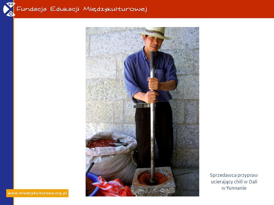 Sprzedawca przypraw ucierający chili w Dali w Yunnanie