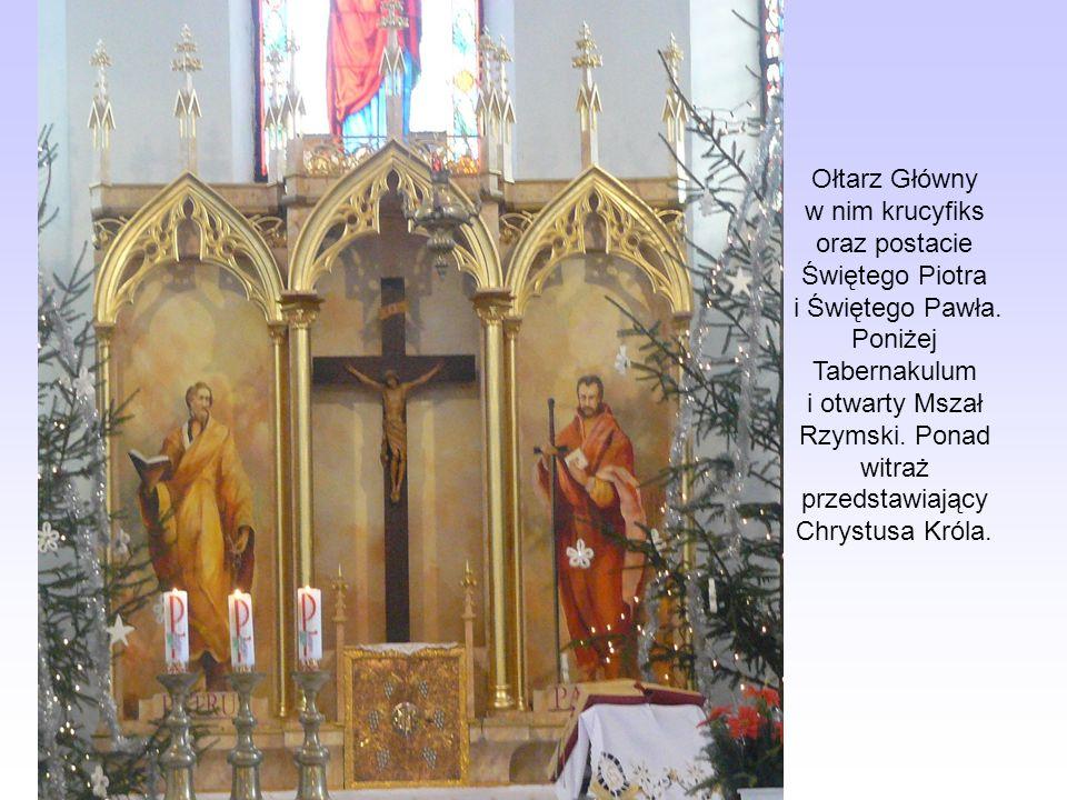 Ołtarz Główny w nim krucyfiks oraz postacie Świętego Piotra i Świętego Pawła. Poniżej Tabernakulum i otwarty Mszał Rzymski. Ponad witraż przedstawiają