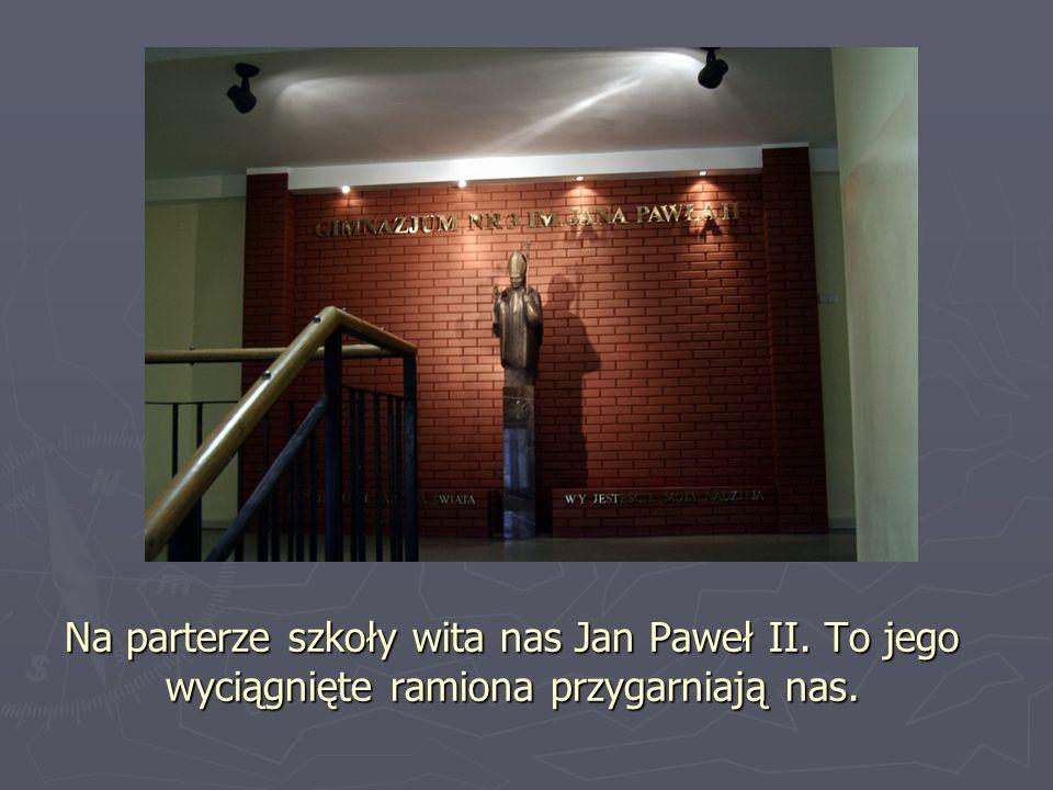 Na parterze szkoły wita nas Jan Paweł II. To jego wyciągnięte ramiona przygarniają nas.