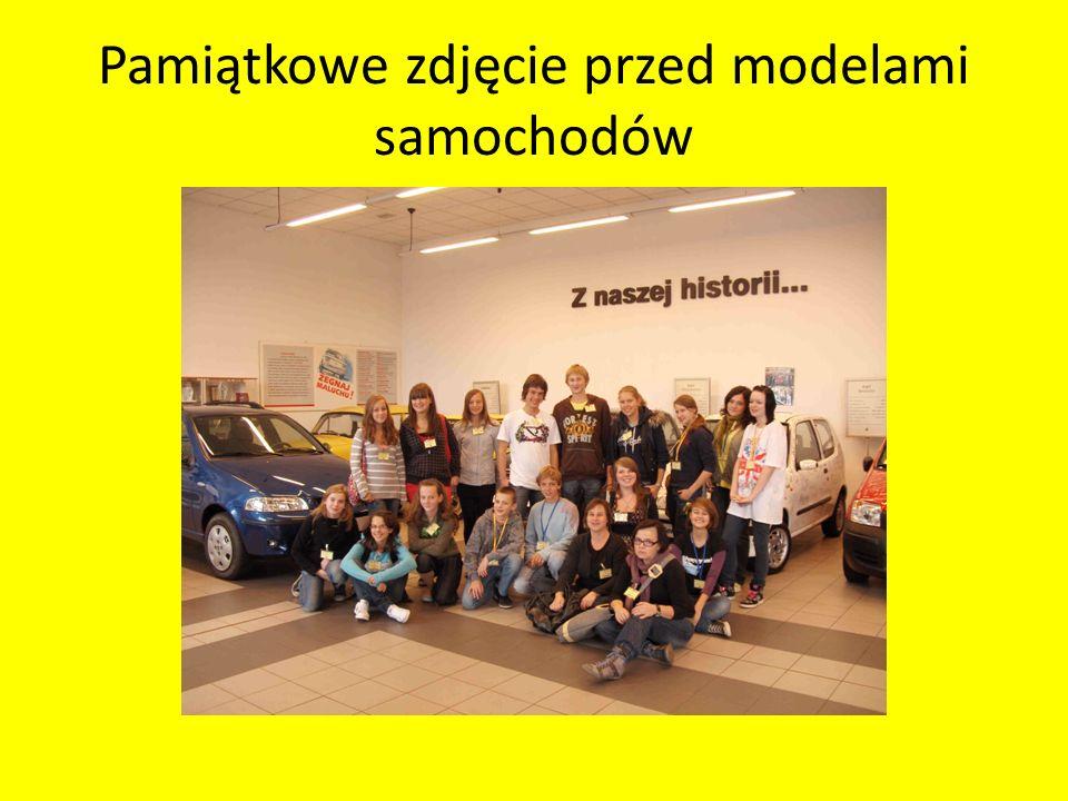 Pamiątkowe zdjęcie przed modelami samochodów