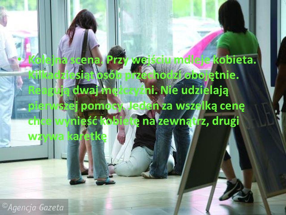 Kolejna scena. Przy wejściu mdleje kobieta. Kilkadziesiąt osób przechodzi obojętnie. Reagują dwaj mężczyźni. Nie udzielają pierwszej pomocy. Jeden za