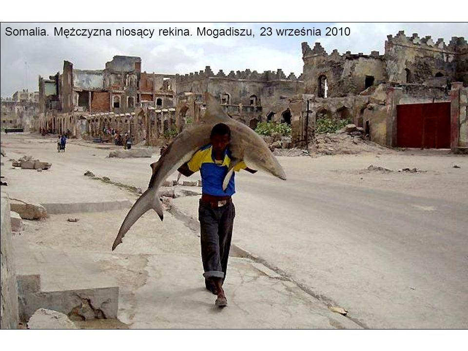 Somalia. Mężczyzna niosący rekina. Mogadiszu, 23 września 2010