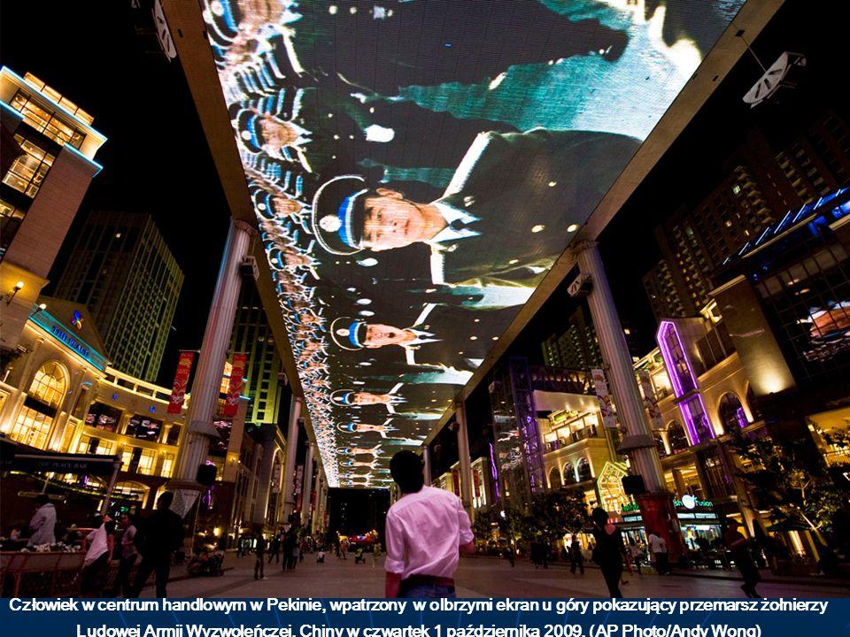 Człowiek w centrum handlowym w Pekinie, wpatrzony w olbrzymi ekran u góry pokazujący przemarsz żołnierzy Ludowej Armii Wyzwoleńczej. Chiny w czwartek