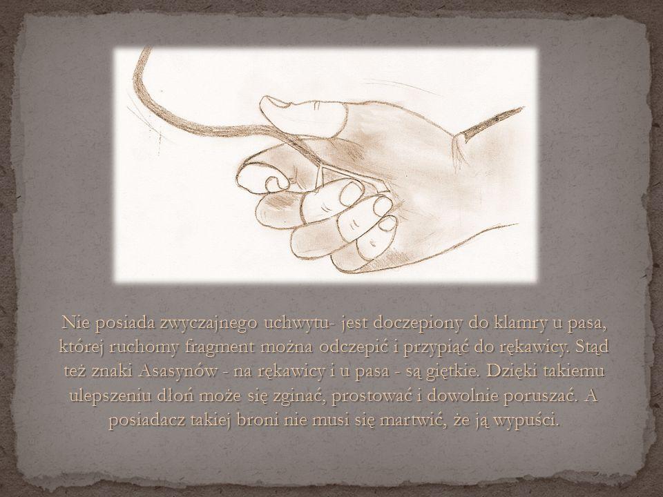 Nie posiada zwyczajnego uchwytu- jest doczepiony do klamry u pasa, której ruchomy fragment można odczepić i przypiąć do rękawicy.