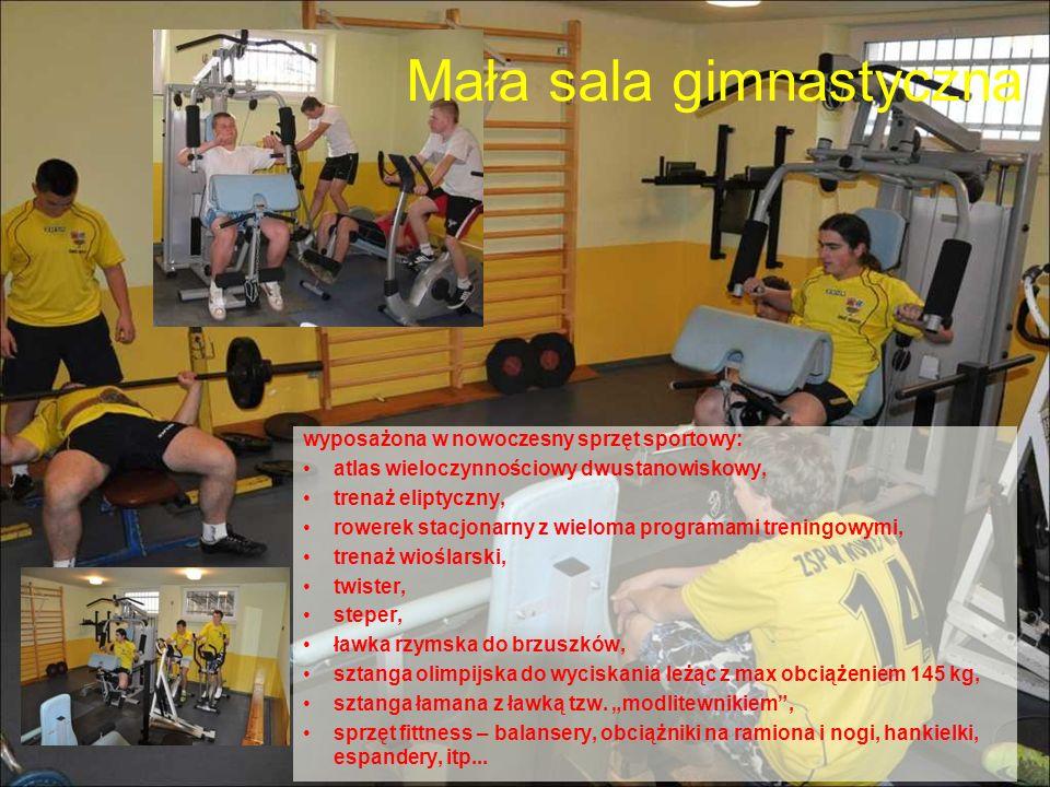 Mała sala gimnastyczna wyposażona w nowoczesny sprzęt sportowy: atlas wieloczynnościowy dwustanowiskowy, trenaż eliptyczny, rowerek stacjonarny z wiel