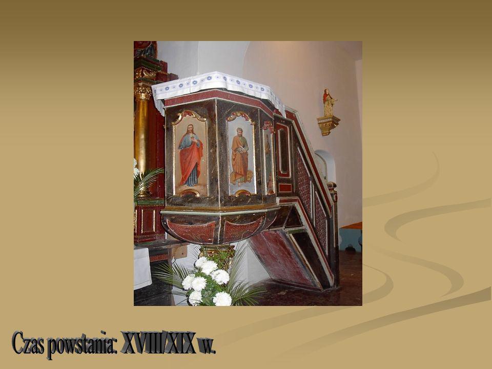 Ambona-przyścienna, drewniana; korpus na planie ośmioboku wsparty na architektonicznej kolumnie z ozdobną złoconą głowicą w typie korynckim (wtórna); spód korpusa w kształcie misy, składającej się z ośmiu wygiętych trójkątów w kolorze brązowym, na których namalowane są ornamenty w kształcie stylizowanych kwiatów lilii ; ścianki parapetu brązowe w kształcie wydłużonych prostokątów, na których umieszczone są malowane na desce wizerunki czterech ewangelistów oraz (na osi sym) Chrystusa; schody i parapet schodów (kratownica) wtórne; baldachim ambony w kształcie korony na planie ośmioboku o wydatnym gzymsie ozdobionym złotymi frędzlami, korona kształtem przypomina koronę książęcą- cztery ceownikowe wygięte ramiona zwieńczone na środku złotą kulą, miejsca miedzy ramionami wypełnione ornamentem owocowym; podniebienie baldachimu z wizerunkiem Ducha Świętego w glorii promienistej na złotym jednolitym tle, (gołębica w kolorze srebrnym).