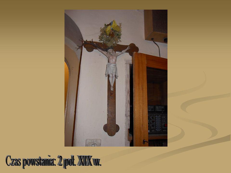 Na dębowym gładkim krzyżu o ramionach zakończonych trójlistnie postać Chrystusa Ukrzyżowanego; głowa w koronie cierniowej przechylona na prawe ramię, twarz o przymkniętych oczach i prostym nosie okolona krótką brodą oraz wijącymi się włosami opadającymi na ramiona; ręce rozłożone na krzyżu w V; lekko podkreślona budowa anatomiczna ciała, karnacja jasna; biodra owinięte w białe perizonium ze złotą lamówką, układające się w drobne fałdy i zawiązane z prawego boku Chrystusa; u góry na krzyżu napis INRI