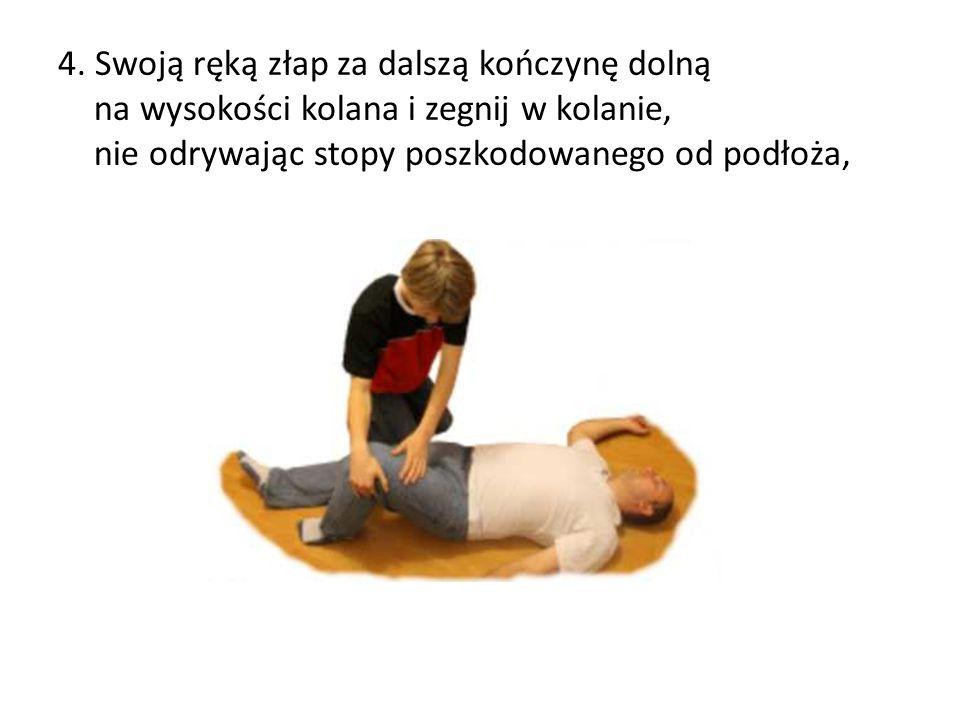 4. Swoją ręką złap za dalszą kończynę dolną na wysokości kolana i zegnij w kolanie, nie odrywając stopy poszkodowanego od podłoża,