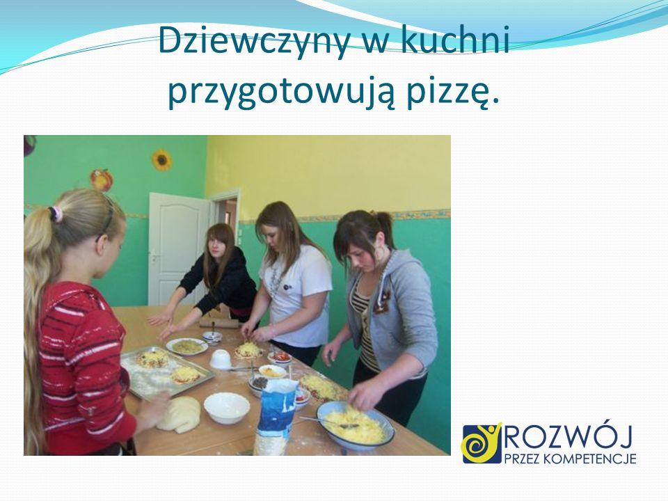 Dziewczyny w kuchni przygotowują pizzę.