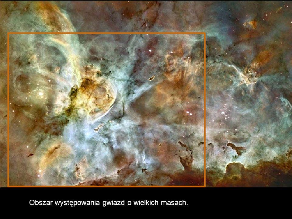 Błyszczące wieże zimnego wodoru wymieszanego z pyłem nakierowane są w stronę dwóch masywnych gwiazd.