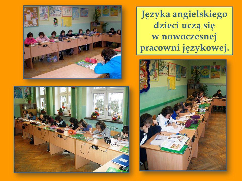 Języka angielskiego dzieci uczą się w nowoczesnej pracowni językowej.