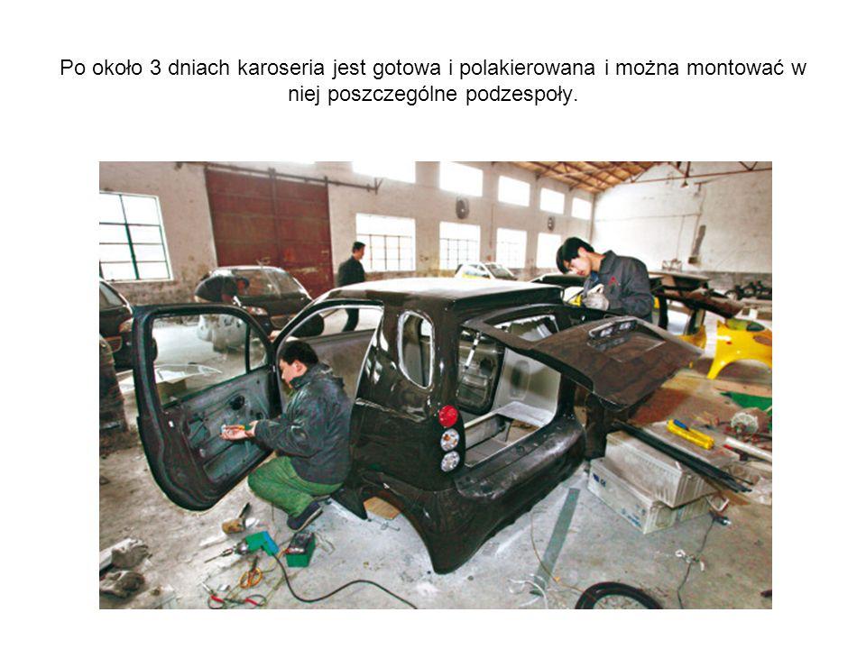 Dwoje pracowników zatrudnionych przy montażu aut
