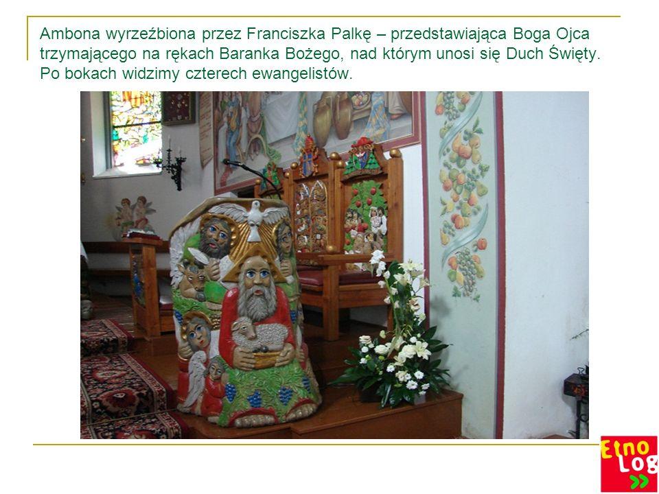 Ambona wyrzeźbiona przez Franciszka Palkę – przedstawiająca Boga Ojca trzymającego na rękach Baranka Bożego, nad którym unosi się Duch Święty. Po boka