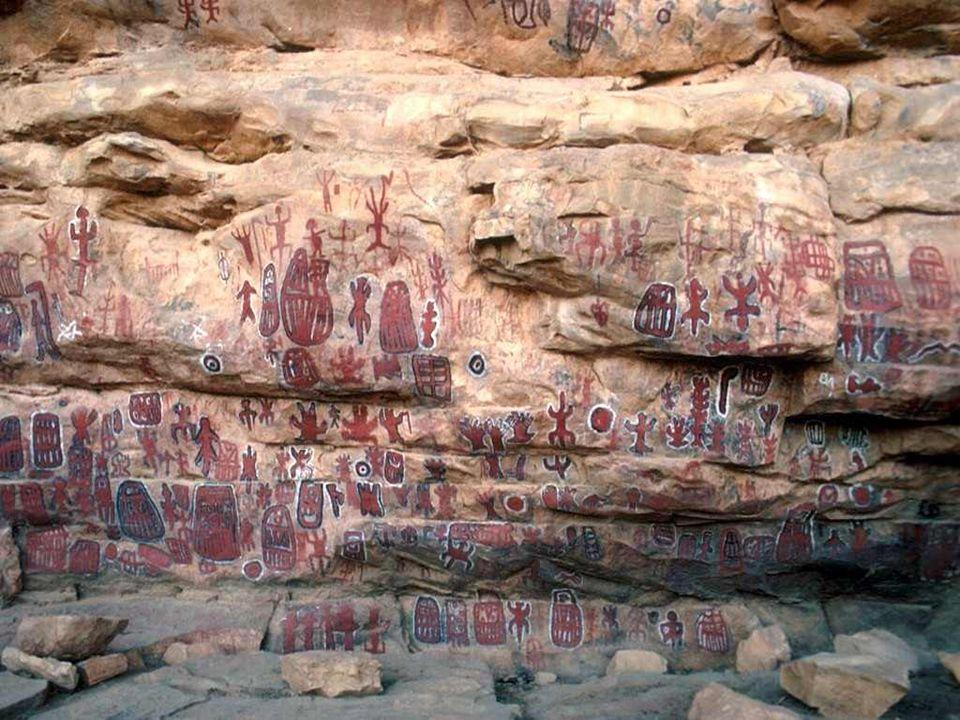 Pod nawisem skalnym (następny slajd), widać ścianę pokrytą symbolicznymi znakami i kolorowymi rysunkami. Wyryte i wymalowane znaki mają swoją symbolik