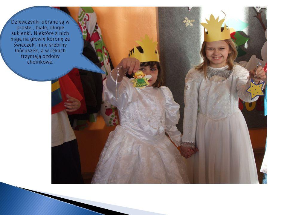Dziewczynki ubrane są w proste, białe, długie sukienki. Niektóre z nich mają na głowie koronę ze świeczek, inne srebrny łańcuszek, a w rękach trzymają