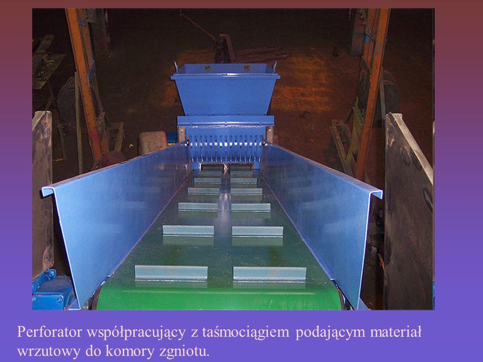 Perforator współpracujący z taśmociągiem podającym materiał wrzutowy do komory zgniotu.