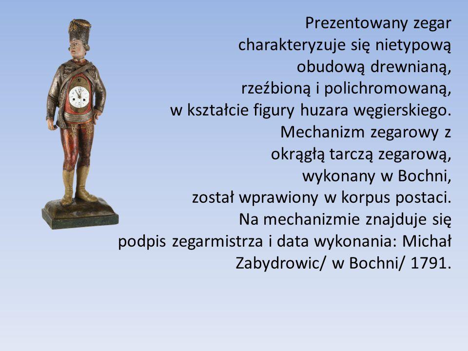 Prezentowany zegar charakteryzuje się nietypową obudową drewnianą, rzeźbioną i polichromowaną, w kształcie figury huzara węgierskiego. Mechanizm zegar