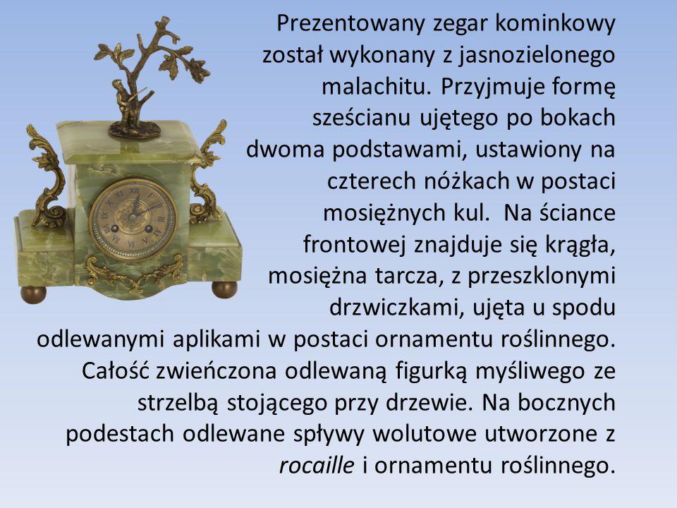 Prezentowany zegar kominkowy został wykonany z jasnozielonego malachitu. Przyjmuje formę sześcianu ujętego po bokach dwoma podstawami, ustawiony na cz