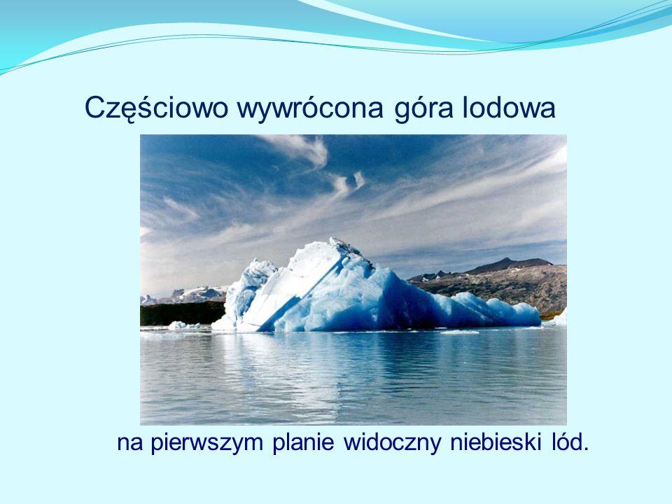 na pierwszym planie widoczny niebieski lód. Częściowo wywrócona góra lodowa