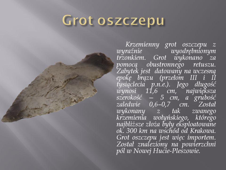 Krzemienny grot oszczepu z wyraźnie wyodrębnionym trzonkiem. Grot wykonano za pomocą obustronnego retuszu. Zabytek jest datowany na wczesną epokę brąz