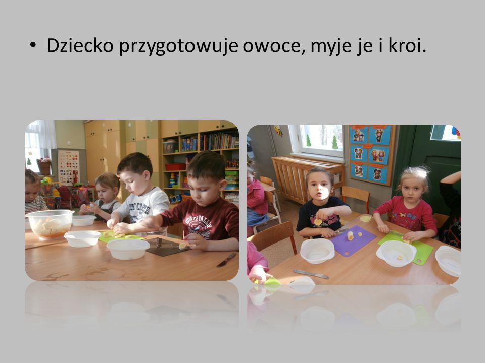 Dziecko przygotowuje owoce, myje je i kroi.