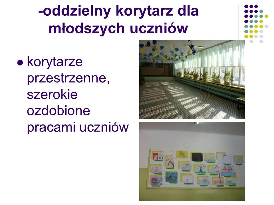 -oddzielny korytarz dla młodszych uczniów korytarze przestrzenne, szerokie ozdobione pracami uczniów