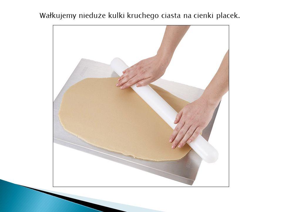 Następnie wykrajamy w placku okrągłe lub inne kształty ciastek przyniesionymi foremkami.