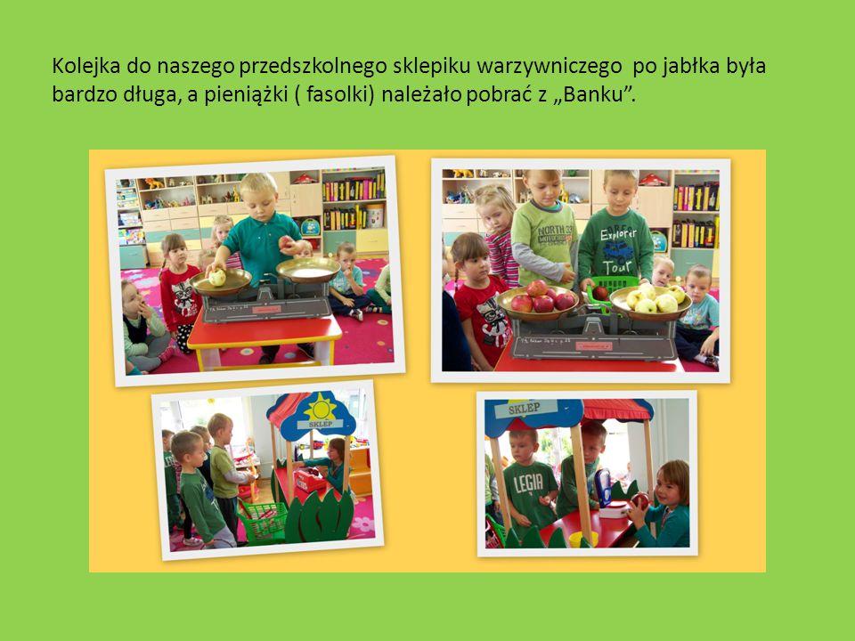 """Kolejka do naszego przedszkolnego sklepiku warzywniczego po jabłka była bardzo długa, a pieniążki ( fasolki) należało pobrać z """"Banku""""."""