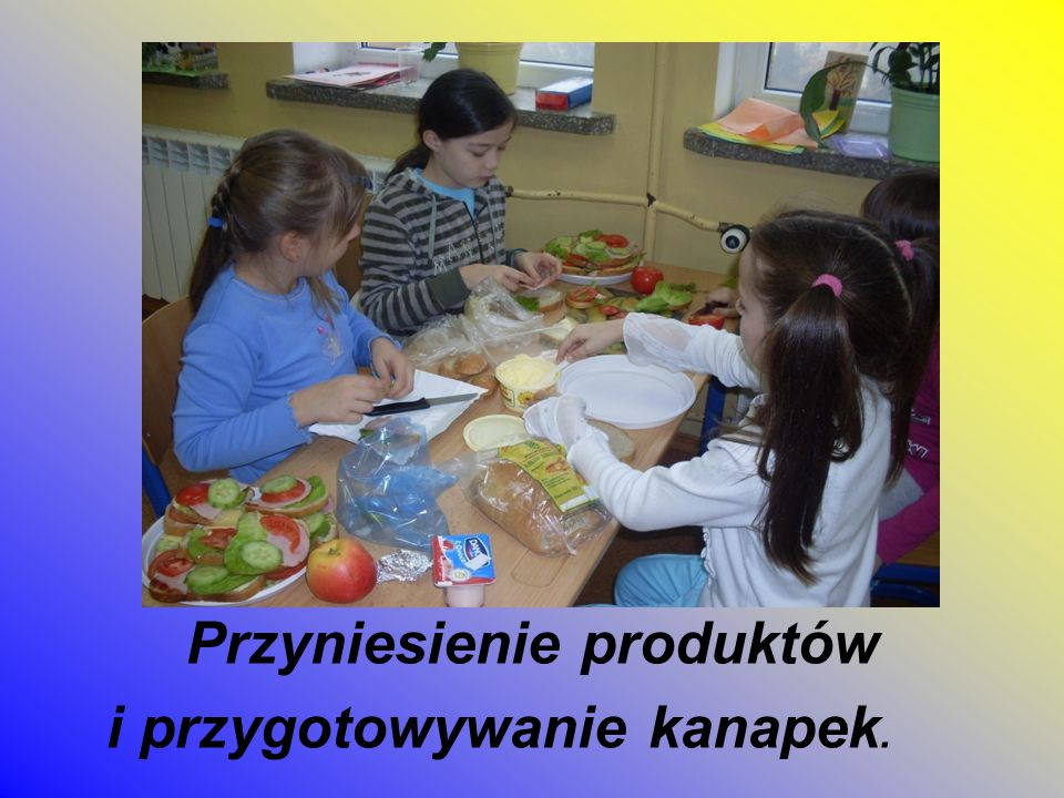 Uczniowie przygotowują stół i ustawiają kolorowe kanapki i smakołyki.