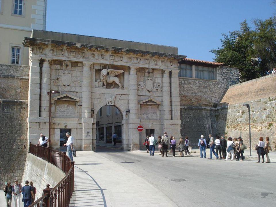 Brama Lądowa (Kopnena vrata) - przebudowana w XVI wieku w jasnym kamieniu. Nad bramą - figura bł.Jana z Trogiru patrona miasta. Po przeciwnej stronie
