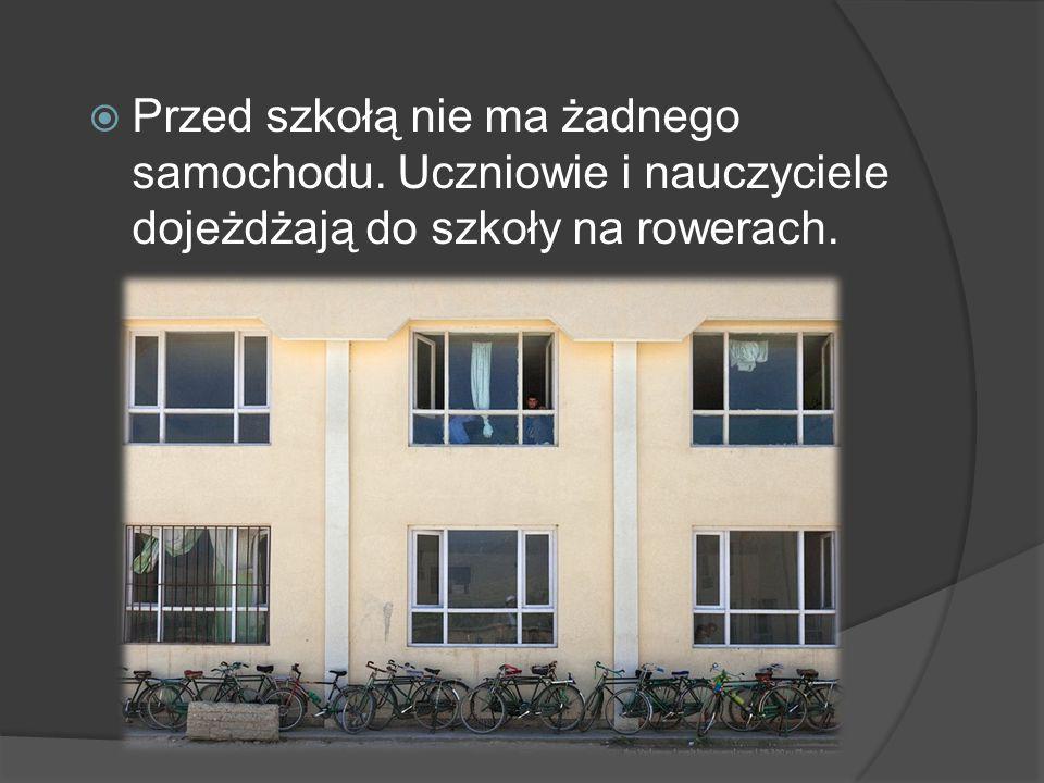 Przed szkołą nie ma żadnego samochodu. Uczniowie i nauczyciele dojeżdżają do szkoły na rowerach.