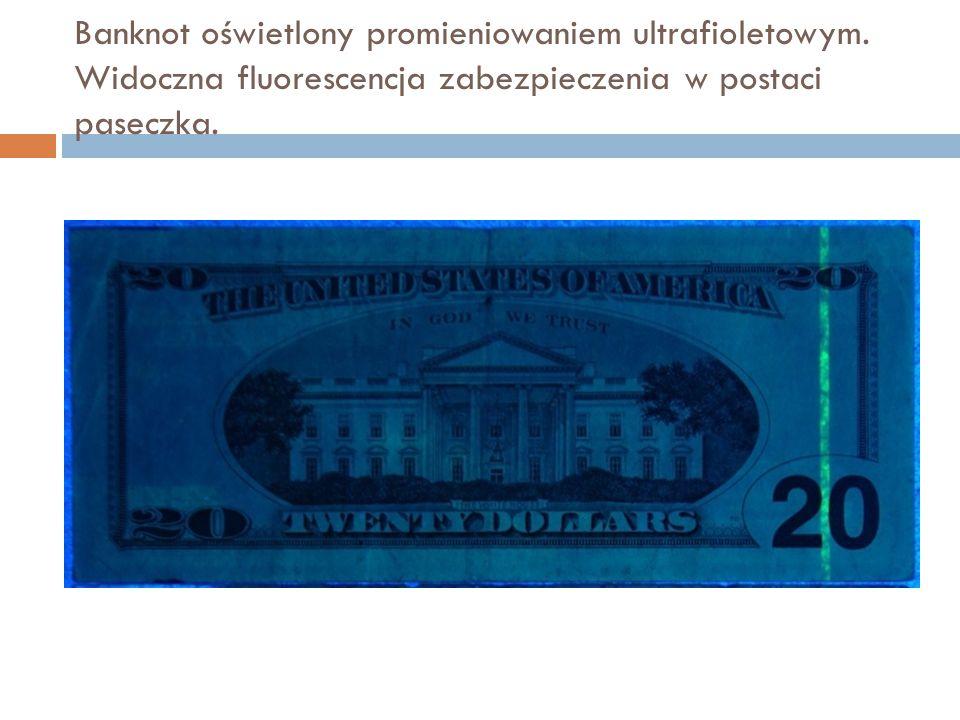 Banknot oświetlony promieniowaniem ultrafioletowym. Widoczna fluorescencja zabezpieczenia w postaci paseczka.