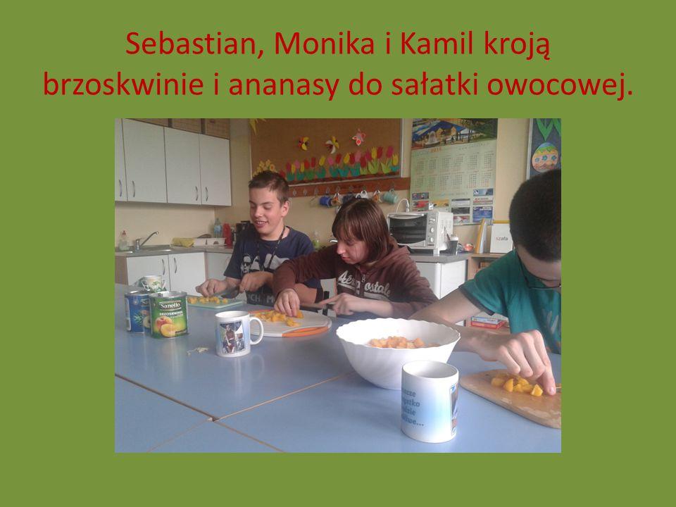 Sebastian, Monika i Kamil kroją brzoskwinie i ananasy do sałatki owocowej.