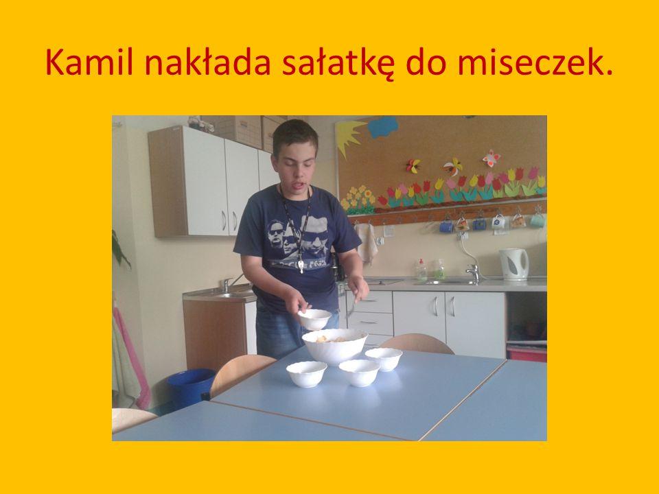 Kamil nakłada sałatkę do miseczek.