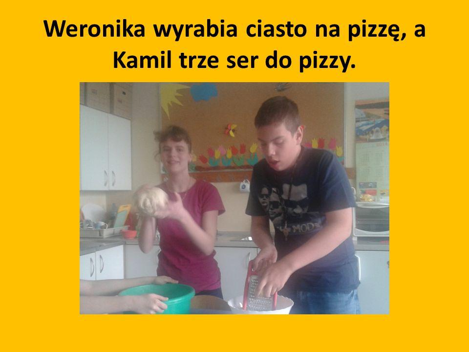Weronika wyrabia ciasto na pizzę, a Kamil trze ser do pizzy.