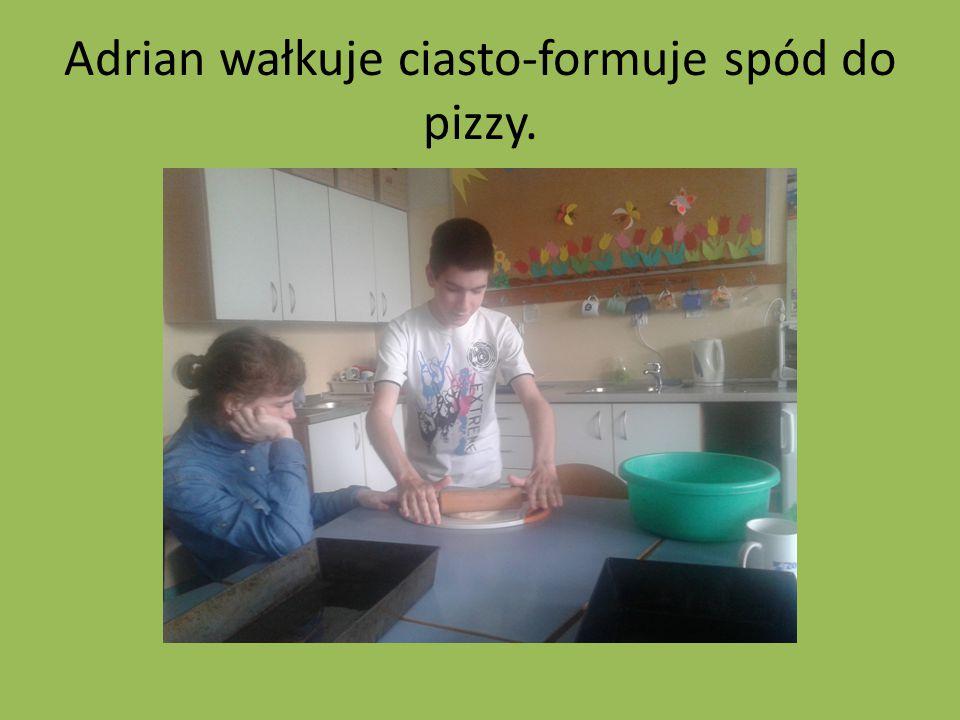 Adrian wałkuje ciasto-formuje spód do pizzy.