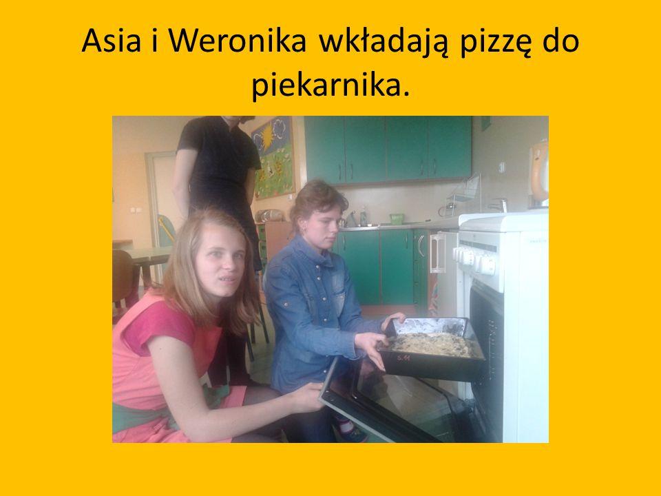 Asia i Weronika wkładają pizzę do piekarnika.