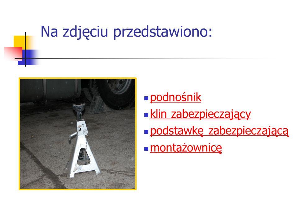 Na zdjęciu przedstawiono: podnośnik podnośnik klin zabezpieczający klin zabezpieczający podstawkę zabezpieczającą podstawkę zabezpieczającą montażownicę montażownicę