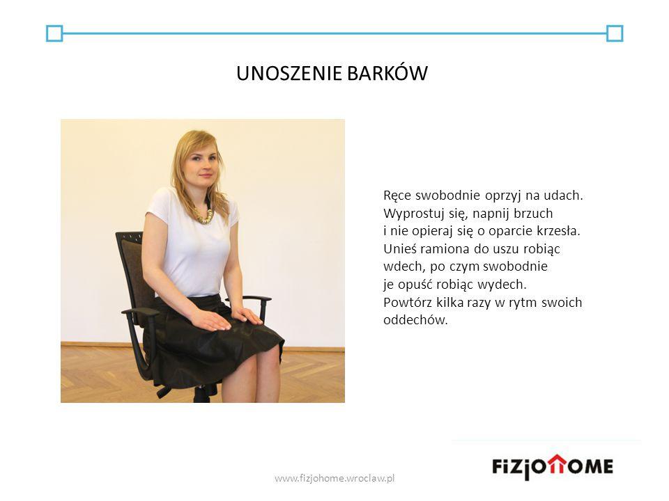 Ręce swobodnie oprzyj na udach. Wyprostuj się, napnij brzuch i nie opieraj się o oparcie krzesła. Unieś ramiona do uszu robiąc wdech, po czym swobodni