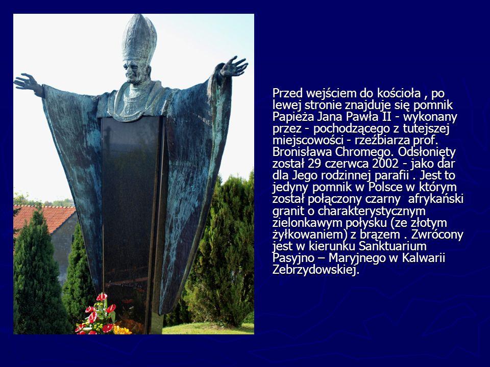 Przed wejściem do kościoła, po lewej stronie znajduje się pomnik Papieża Jana Pawła II - wykonany przez - pochodzącego z tutejszej miejscowości - rzeź