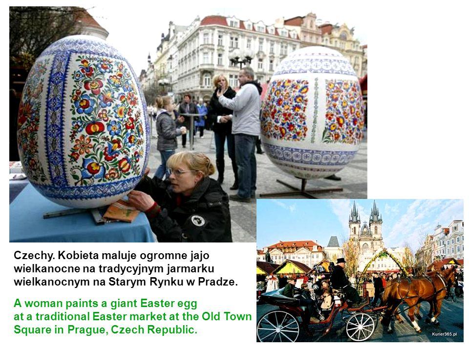 Czechy. Kobieta maluje ogromne jajo wielkanocne na tradycyjnym jarmarku wielkanocnym na Starym Rynku w Pradze. A woman paints a giant Easter egg at a