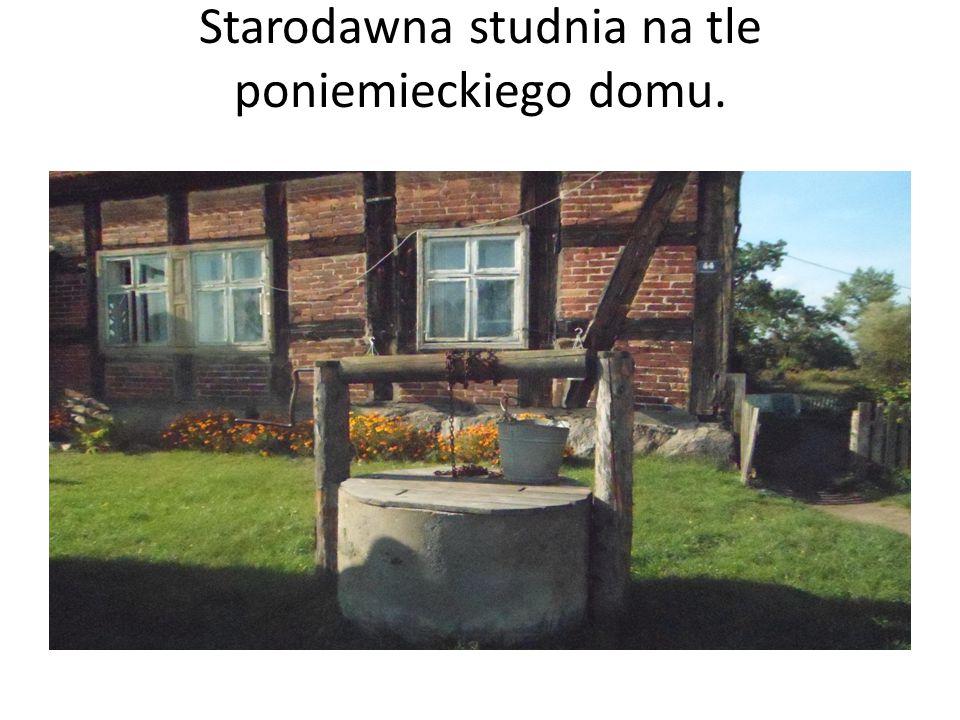 Starodawna studnia na tle poniemieckiego domu.