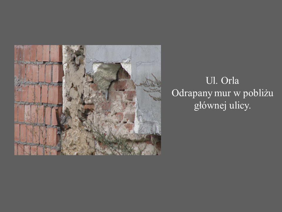 Ul. Orla Odrapany mur w pobliżu głównej ulicy.